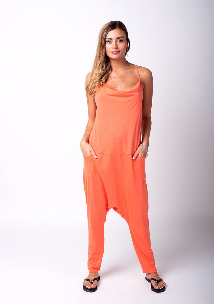 Full frontal pose with hands in pockets, wearing harem trousers style coral jersey jumpsuit.