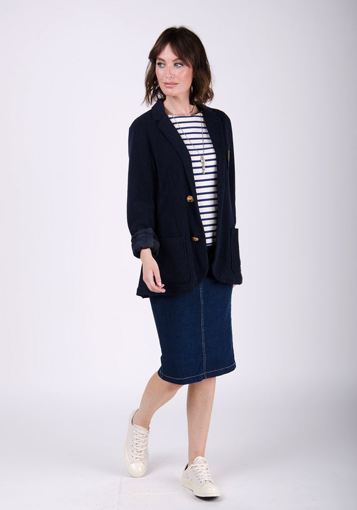 Full-front pose facing to her right, wearing WASH Clothing Company's comfortable denim skirt paired with black blazer.