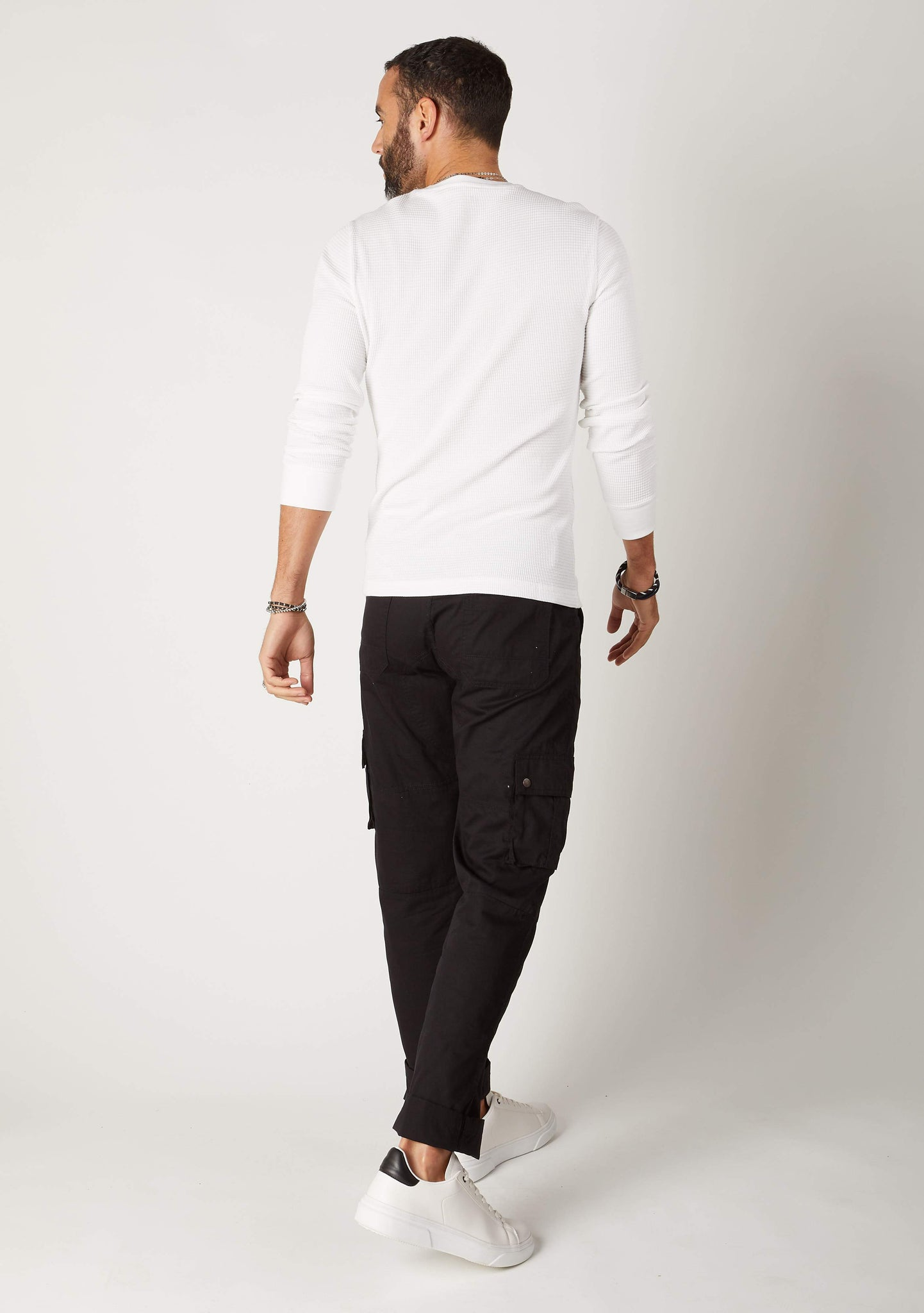 Rear full-length pose mens lightweight black cotton cargo pocket pants.