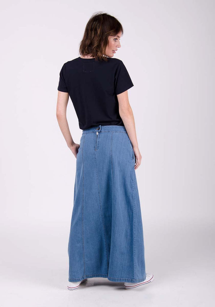 Matilda style pale wash denim skirt with hands on side pockets, showing back zip.