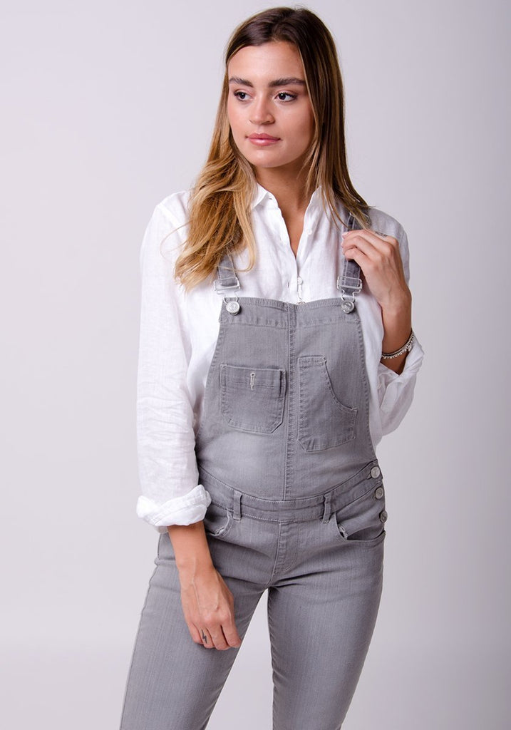 Two-thirds frontal pose looking to her right, showing upper portion of ladies skinny fit dungarees with pockets.