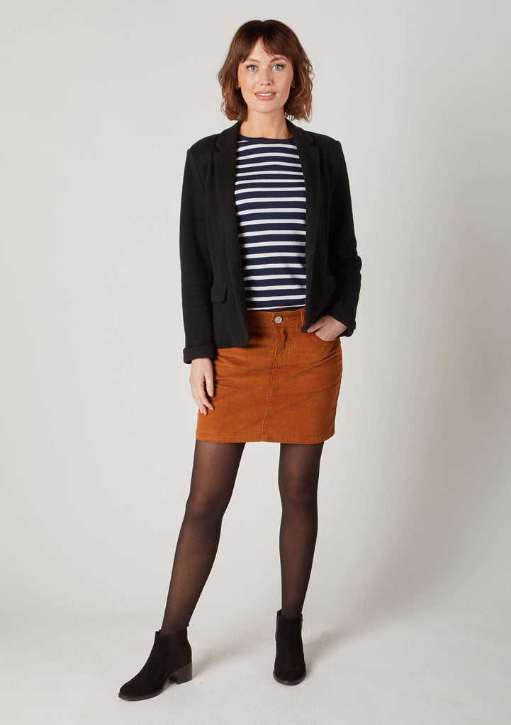 Full-length pose wearing Jacey toffee brown mini cord skirt with hand in side pocket.