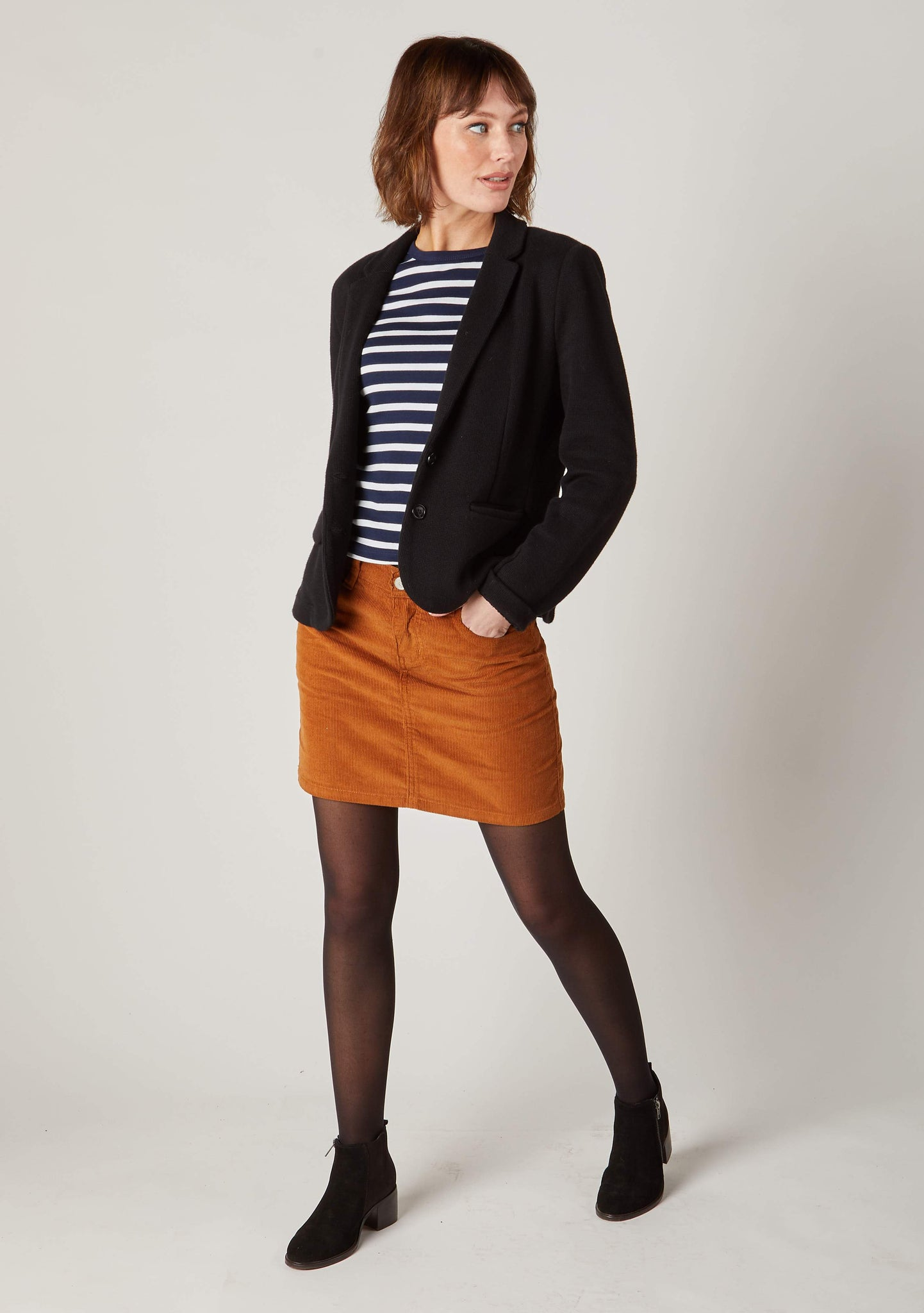 Front view of mid-thigh length brown cord skirt with hand in side pocket.