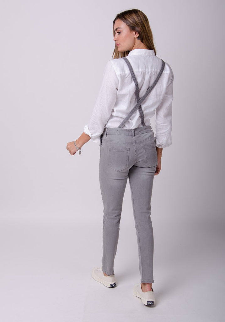 Full rear pose, showing straps and back pockets of faded grey, skinny dungaree.