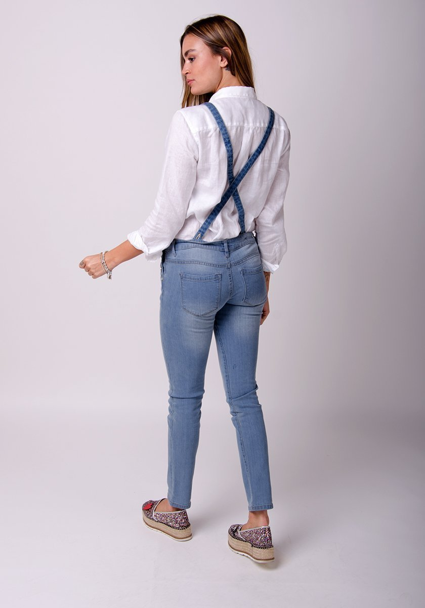Full rear pose, showing straps and back pockets of pale blue, skinny dungaree.
