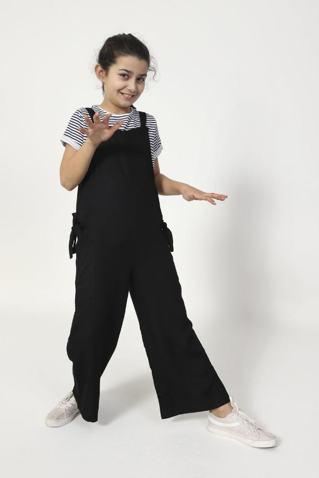 Full-frontal stretching left leg, wearing WASH Clothing Company's girls cropped dungarees.