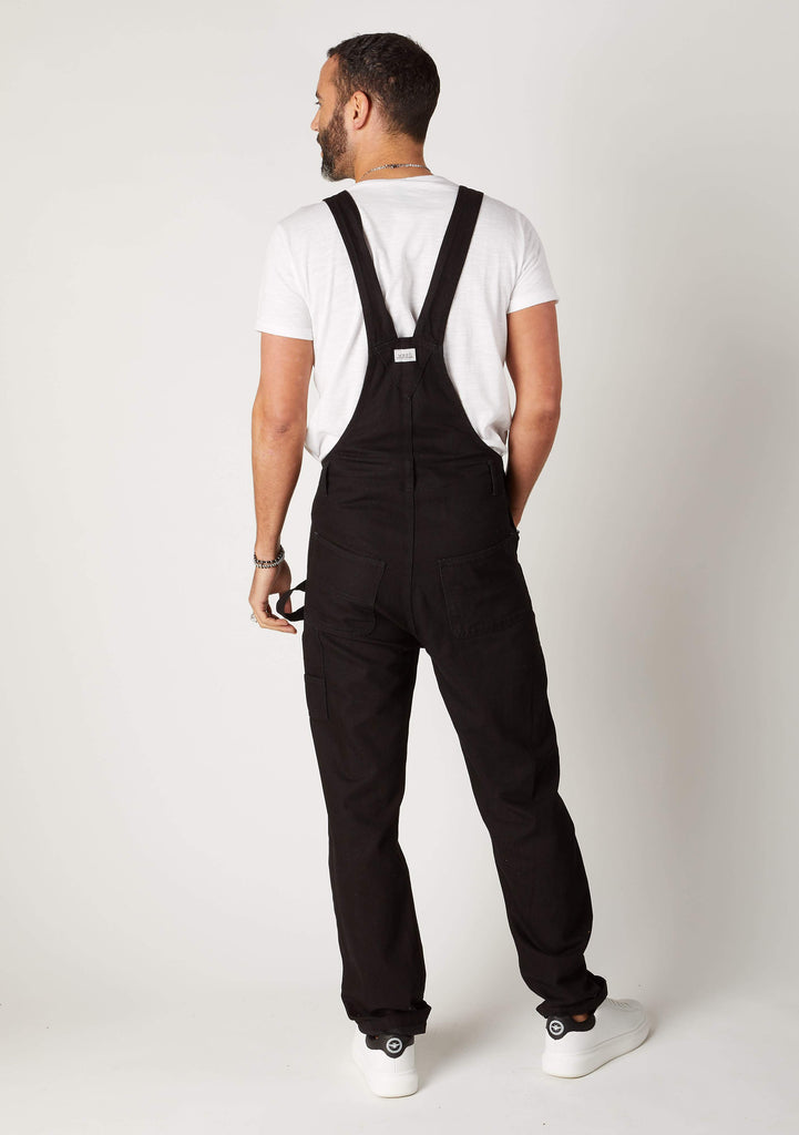 Rear view full-length pose men's black bib-overalls showing back of straps
