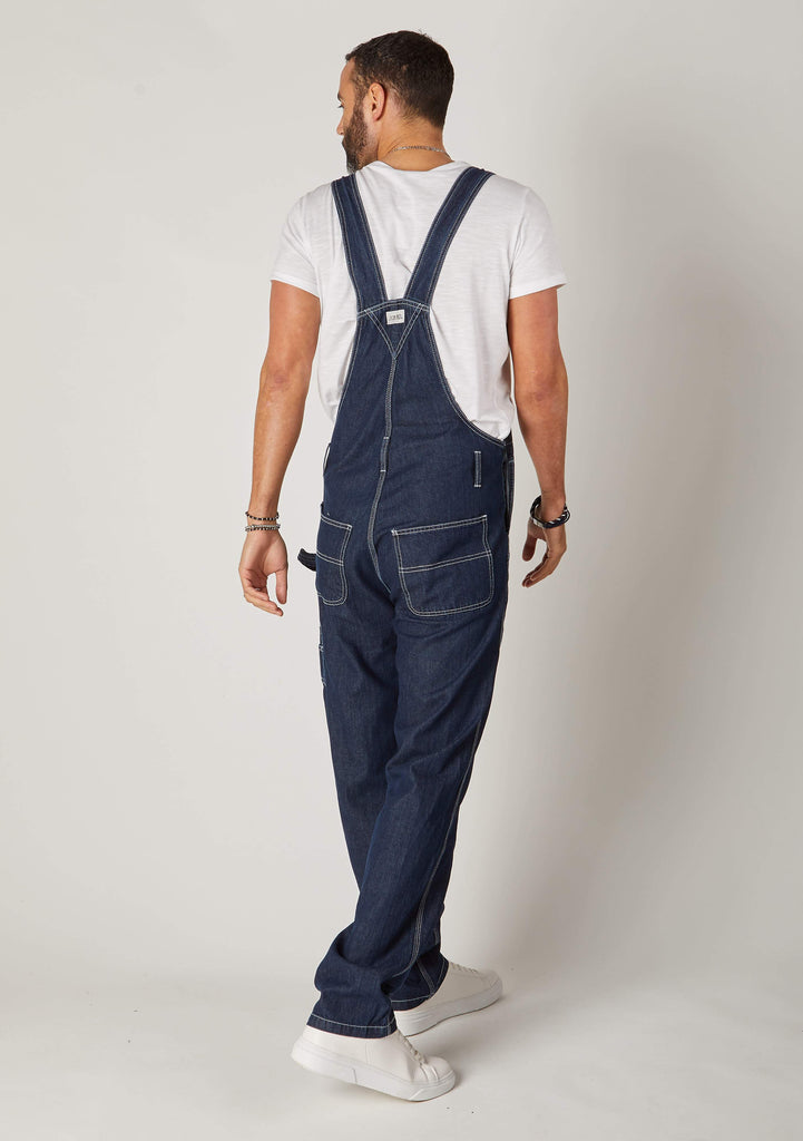 Rear view full-length pose men's blue bib-overalls showing back pockets