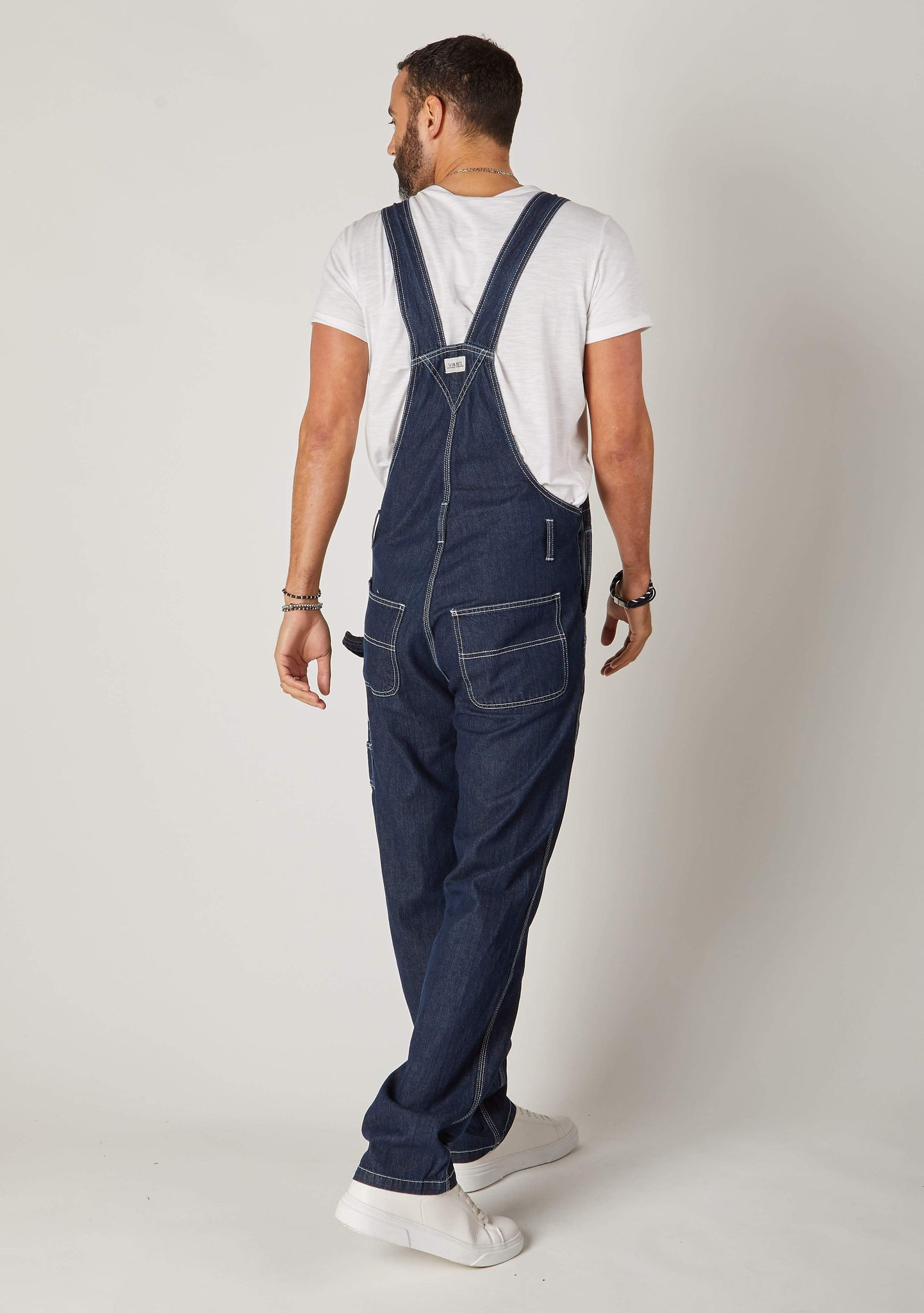 Rear full-length pose mens dark blue bib-overalls showing back of straps.