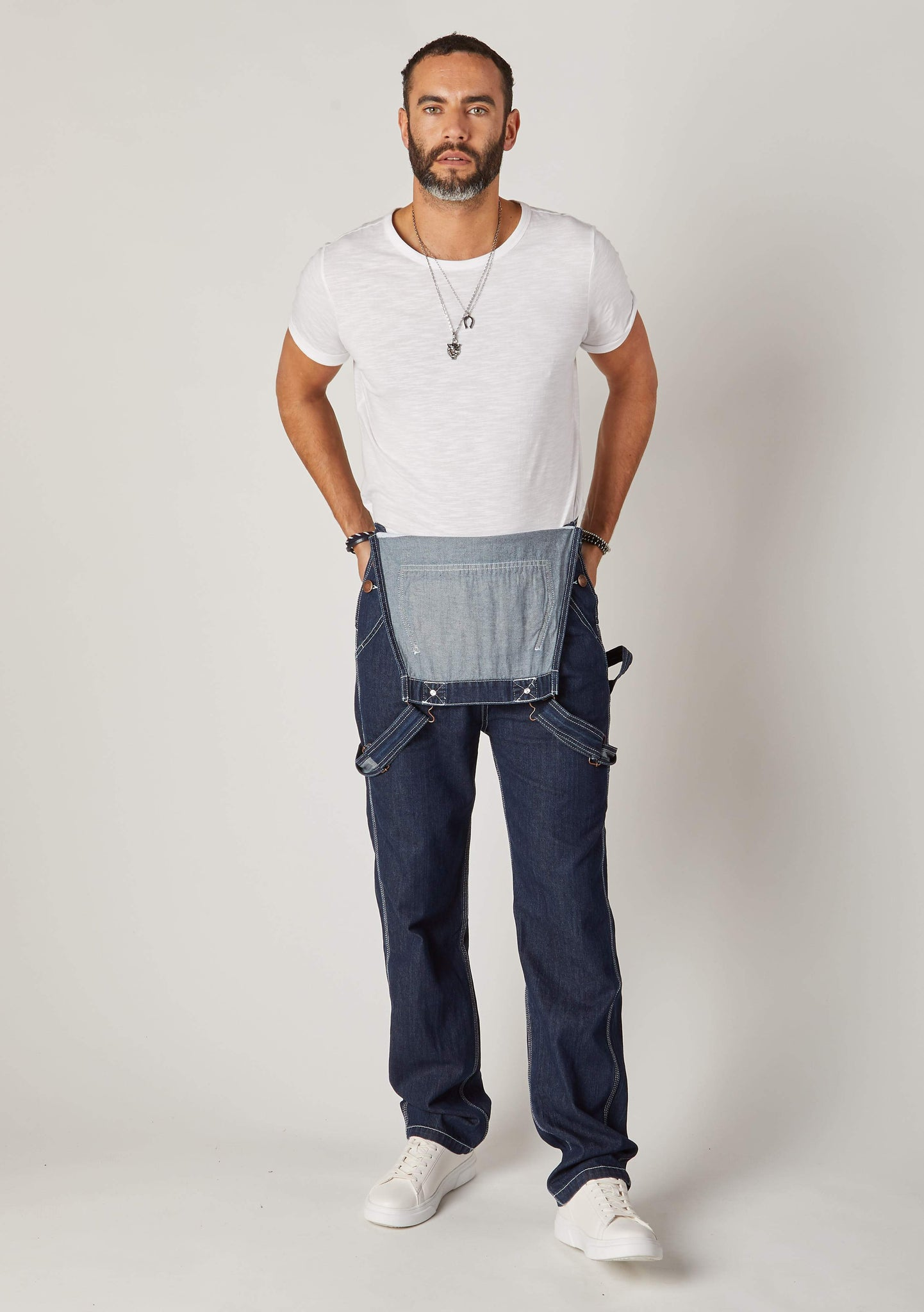 Front full-length pose of men's dark blue denim with contrast stitching denim overalls styled with bib down.