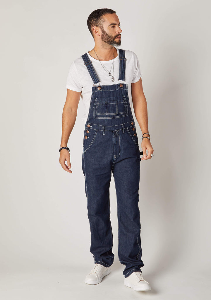 Front full-length pose Maddox dark blue denim loose fit bib-overalls for men.
