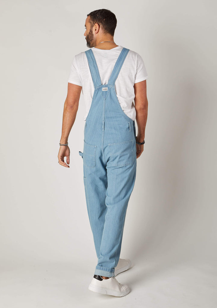 Rear view full-length pose men's light blue bib-overalls showing back pocket and hammer loop