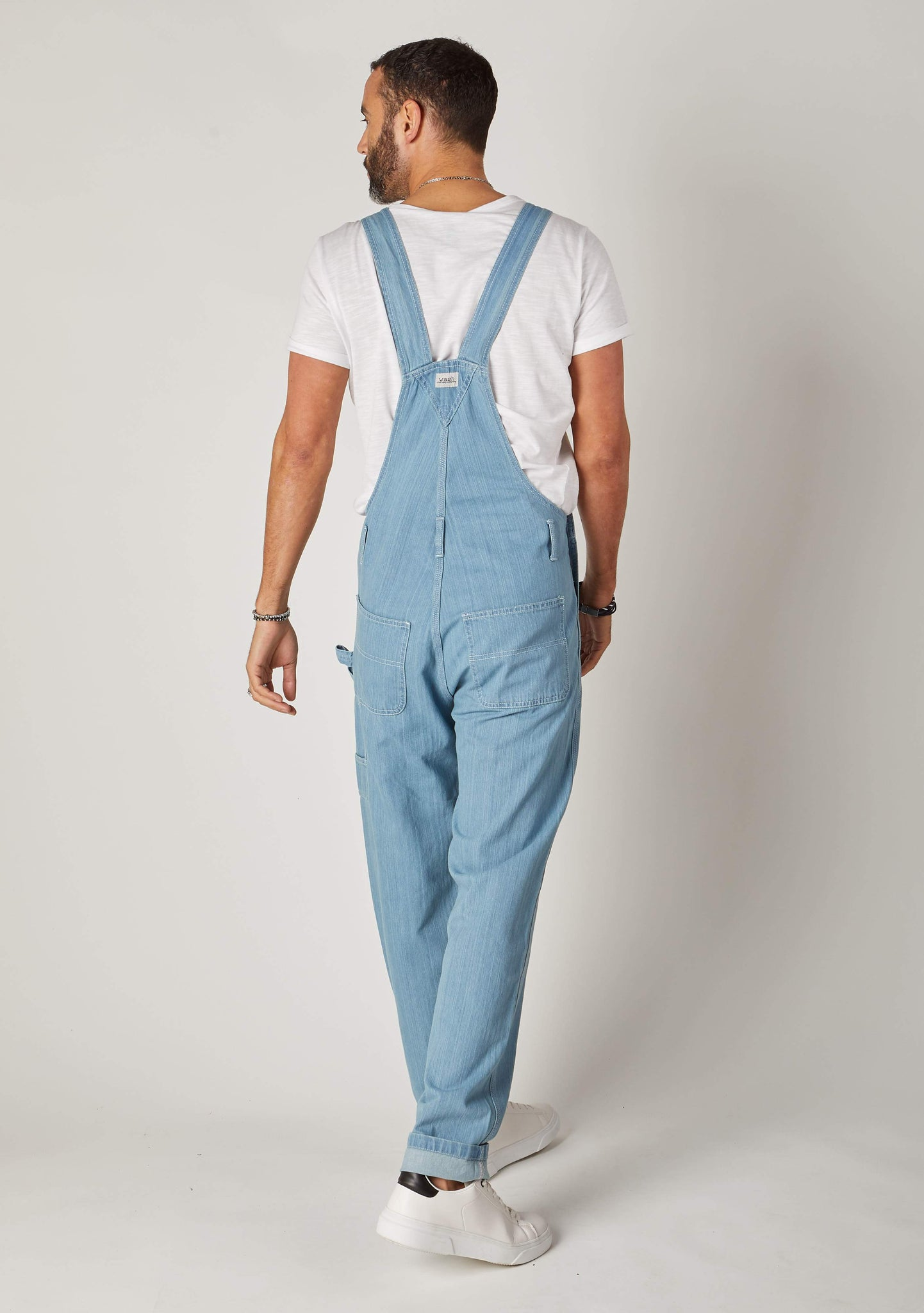 Rear Shot full-length pose mens blue bib-overalls showing back pockets, hammer loop and belt loops.
