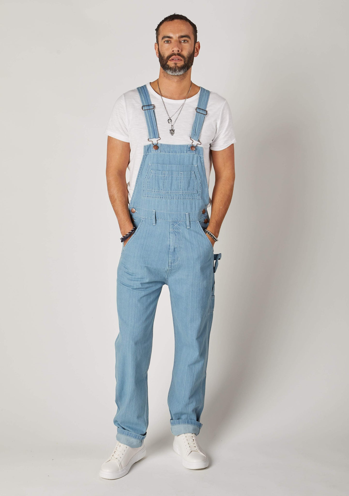 Front full-length pose of Maddox Pale blue denim loose fit bib-overalls for men.