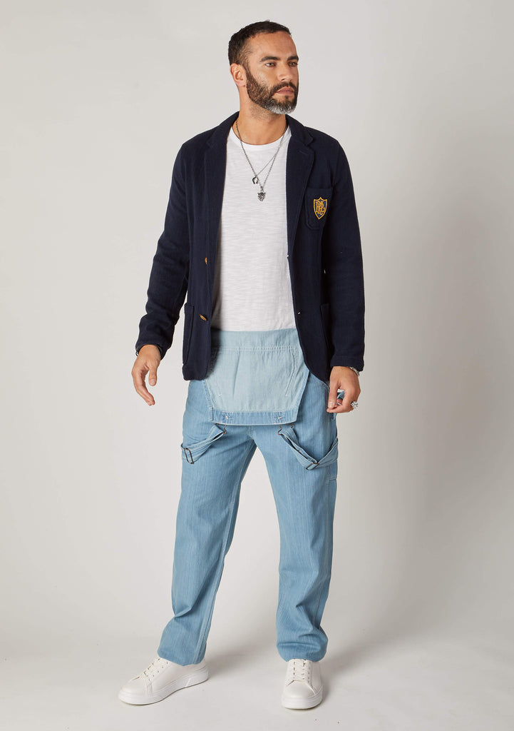 Front full-length pose of men's palewash denim bib and brace overalls styled with bib down.