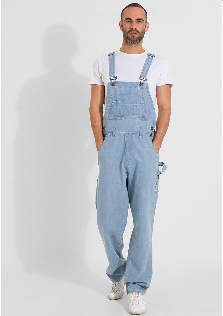 Full frontal pose with hands in front pockets, wearing durable palewash overalls.