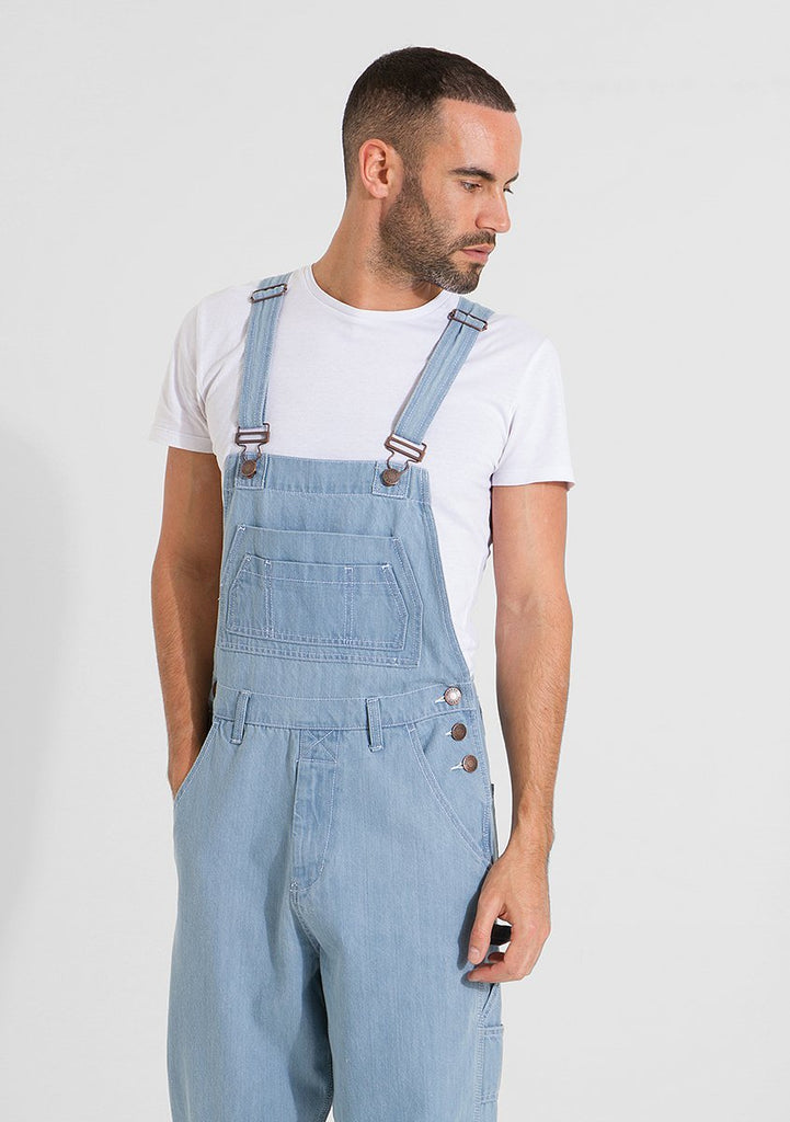 Two-thirds frontal pose looking to his left, wearing Maddox urban-style 10oz palewash denim bib-overalls.