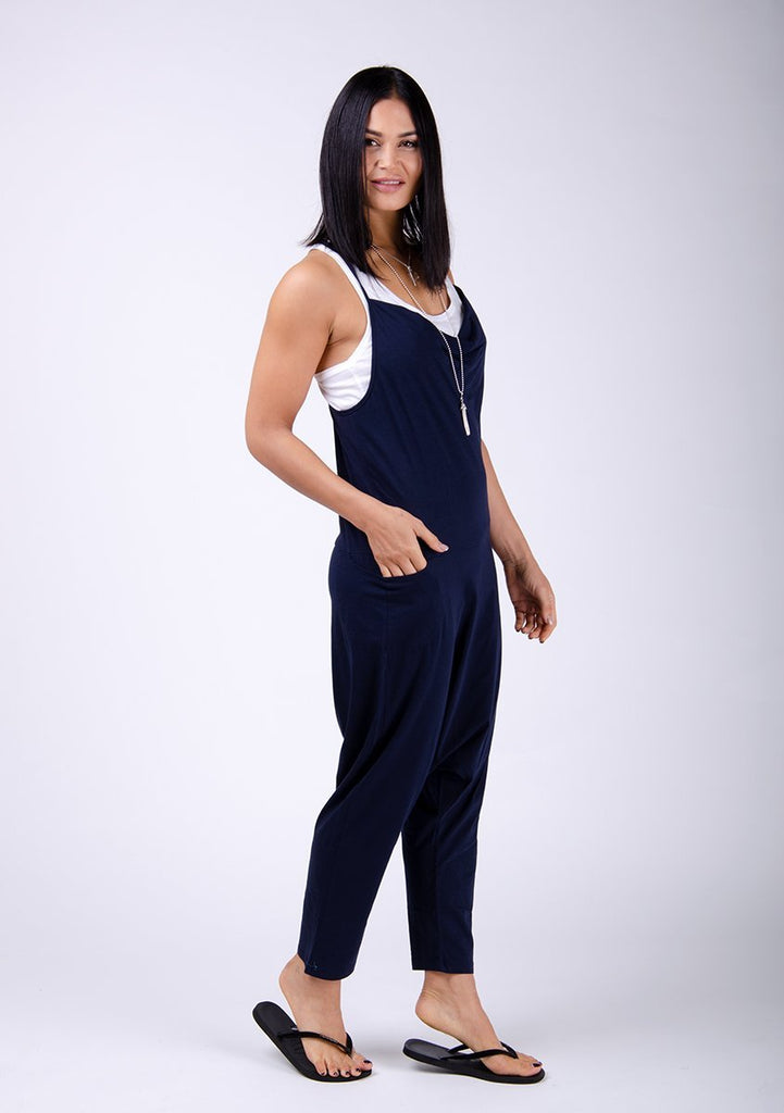 Full frontal pose twisting to her left with hand in side pocket. Wearing Cindy-style navy jersey jumpsuit.