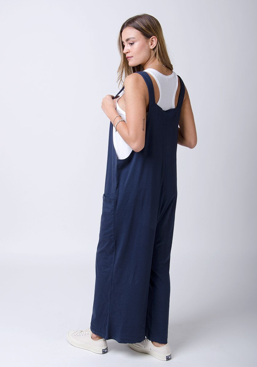 Side-rear full-length pose with Amber-style, navy, cotton jersey, relaxed-fit overalls holding adjustable straps.