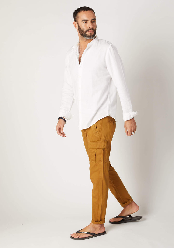 Side pose of Radcliffe gold colour organic cotton cargo pants for men showing pocket on leg