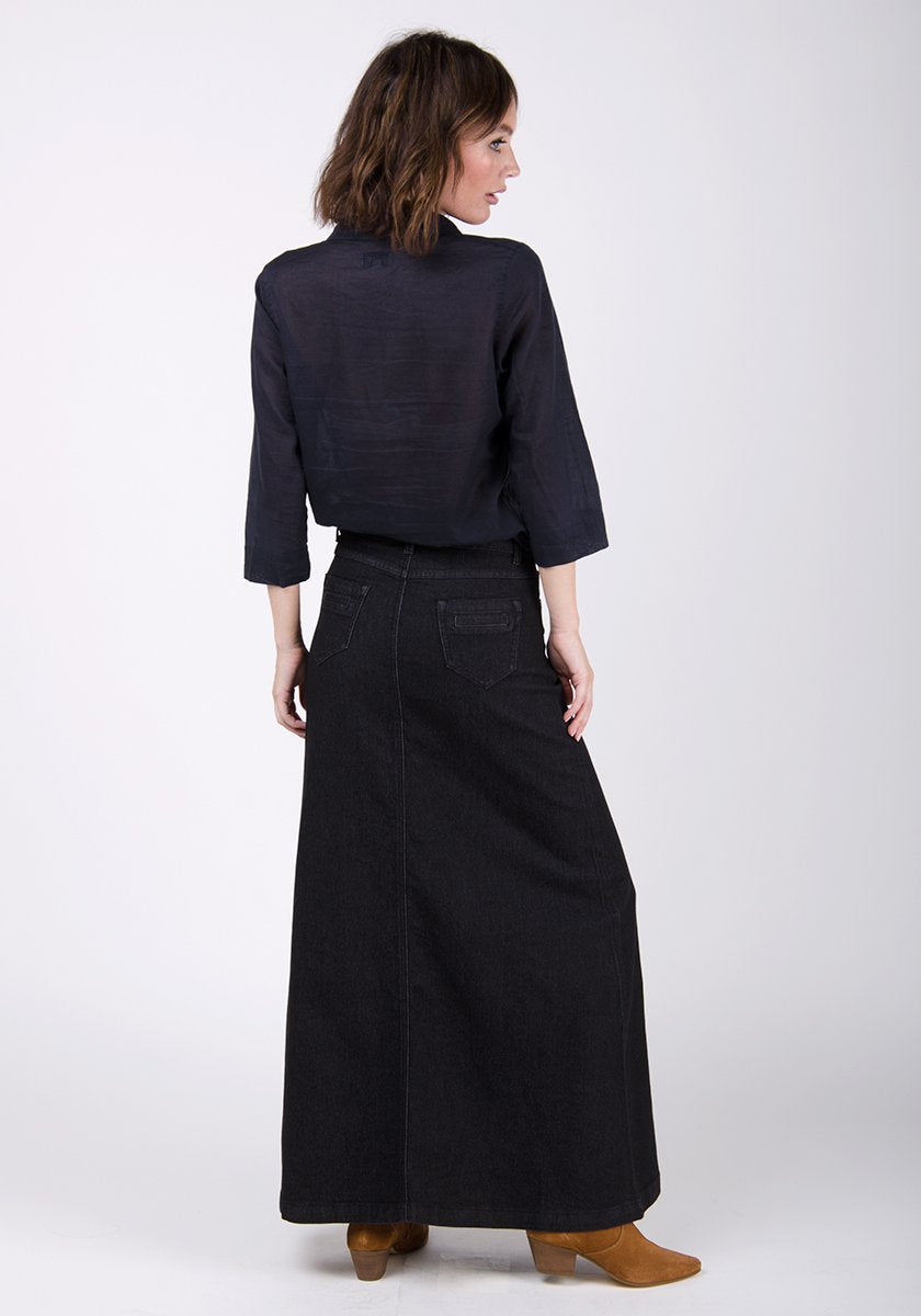 Full-length rear pose wearing WASH Clothing Companys black A-line denim skirt with no back split.