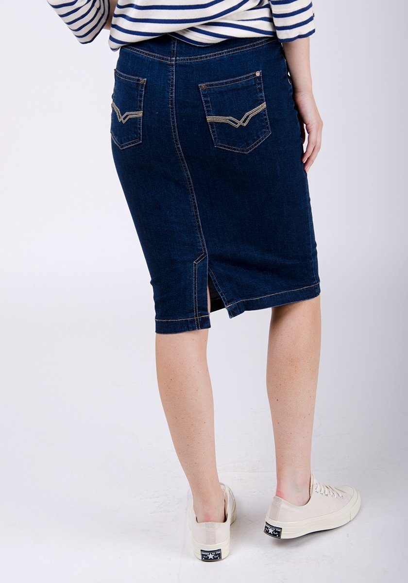 Half-rear pose wearing darkwash denim skirt focussing on denim texture, back pockets and back-split.