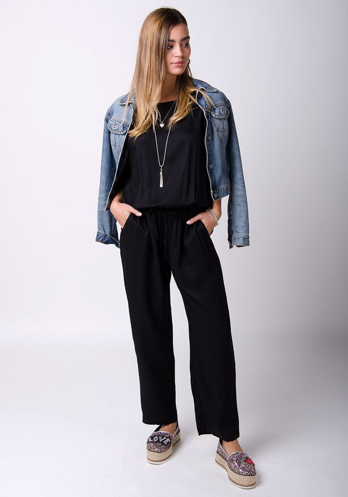 Full-frontal pose resting on right hip with denim jacket over shoulders, wearing black viscose jumpsuit.
