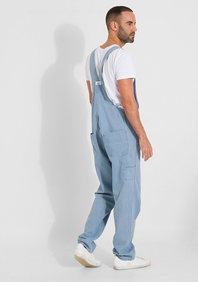 Full frontal-side pose wearing worn-in style bib-overall with a relaxed-fit bib overall.