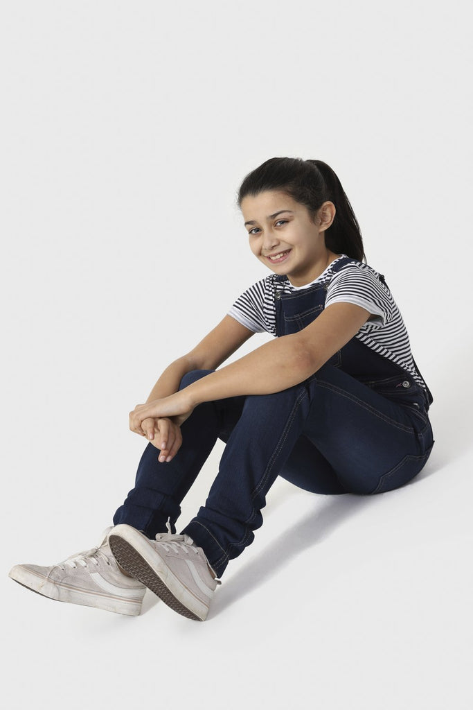 Girl sitting on floor with stretched legs, wearing slim fit denim dungarees with adjustable straps.