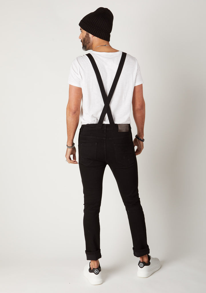 Full rear pose focussing on slim adjustabe straps on Trafford style biker overalls.