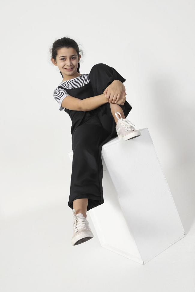 Sitting on box, wearing WASH Clothing Company's girls black, viscose jumpsuit.