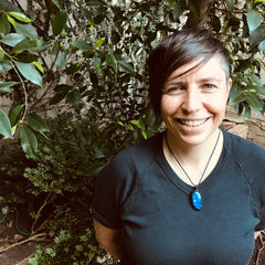 Tara Brooks is Walking Nature's Path owner and naturopath. Standing in front of green tree.
