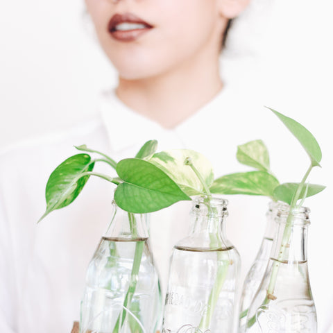 Women in white shirt holding glass bottles with herbs in them