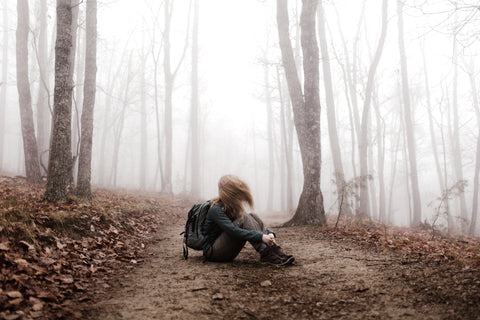 Woman sitting alone in forest, wind sweeping through her hair.