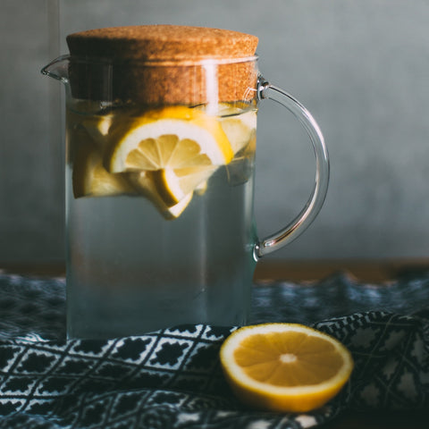 Large glass jug of water with lemon pieces in it