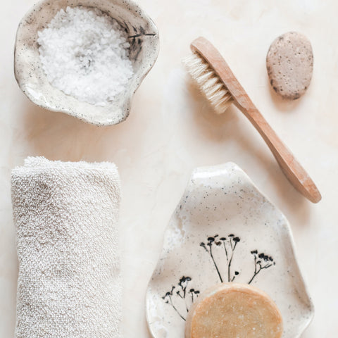 A dry brush, towel and salt on a tray