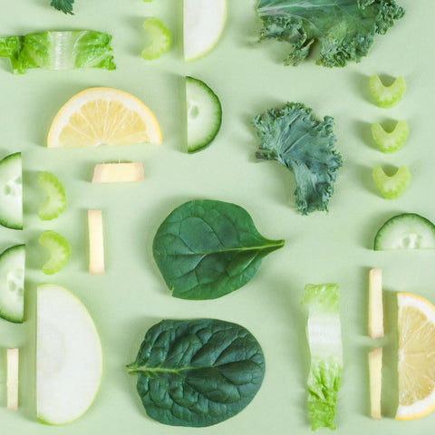 Lettuce, lemon, kale, celery and cucumber pieces on a green table