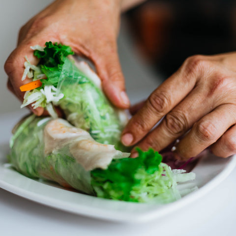 Two hands holding a vegan rice paper roll with green vegetables.