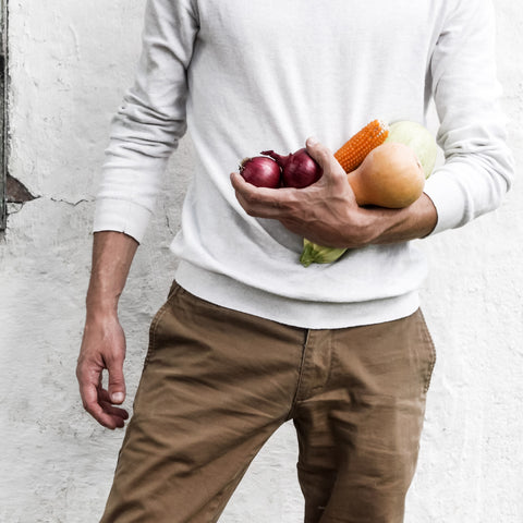 Man in white shirt holding vegetables