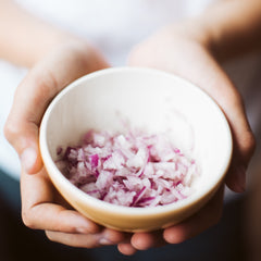 person holding a bowl of raw red onion for their immune healthy diet