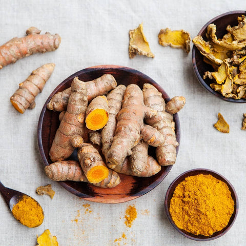 Golden pieces of fresh and powdered ginger in a bowl
