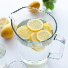 Large glass jug with drinking water and lemon
