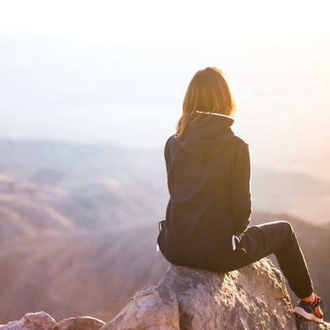 Woman sitting on a mountain top looking over a valley.
