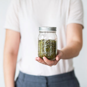 Man holding a jar of beans waiting for vegan naturopath consultation.