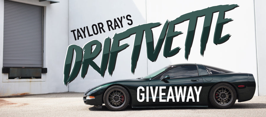 Taylor Ray's Driftvette Giveaway desktop banner showing his 2001 Chevrolet Corvette in racing green parked in front of a loading dock with a white washed wall in the background