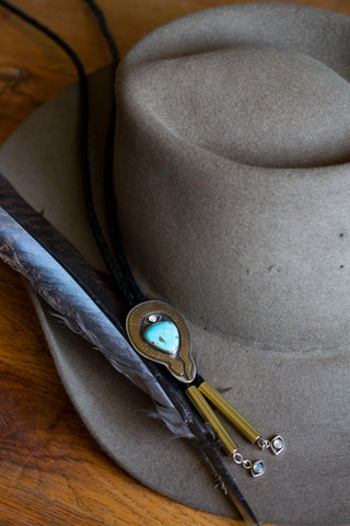 bolo tie on feather and cowboy hat