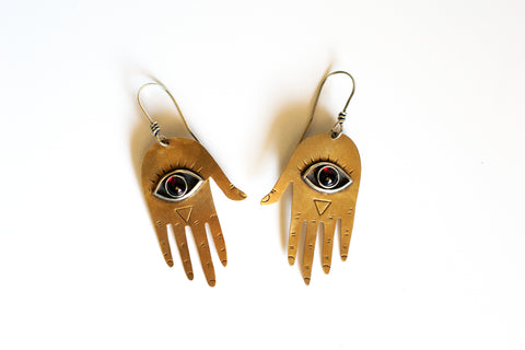 Two brass hand shaped earrings with red garnet eyeballs in the center of the palms on a white background.