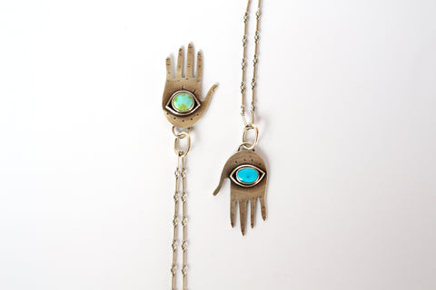 Two silver hand pendants with turquoise eyeballs in the palm on a white background.