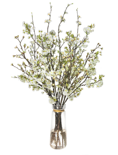 Mixed blossom branches in glass vase with gold band