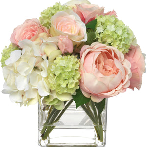 Pale pink hydrangea and rose bouquet in glass cube